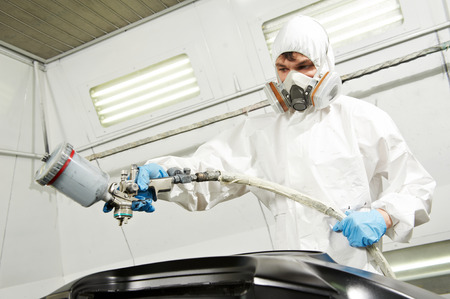 auto mechanic worker painting car bumper at automobile repair and renew service station shop by spraing black color paint photo
