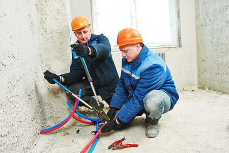 mounter: two repairman engineer installing house heating system at interior construction site Stock Photo