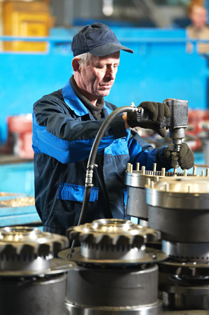 adult industrial worker during heavy industry machinery assembling on production line manufacturing workshop at factory photo