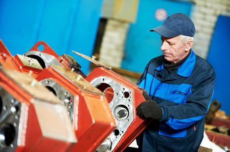 linea de produccion: adulto experimentado trabajador industrial en la maquinaria de la industria pesada montaje en taller de fabricaci�n de la l�nea de producci�n Foto de archivo