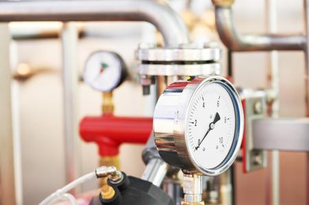 暖房のボイラー室の圧力計、パイプおよび蛇口のバルブのクローズ アップ