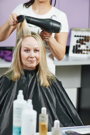 parlour: hairdresser drying hair with blow dryer of woman client at beauty parlour after highlighting Stock Photo