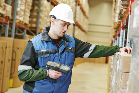 storage warehouse: worker man in uniform scanning package in modern warehouse