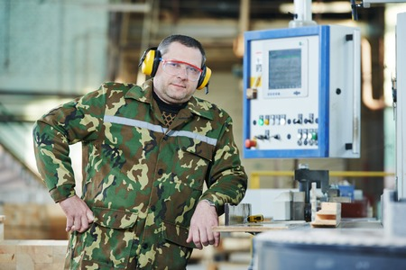 Portrait of woodworking industry factory worker near cnc machine at factory photo