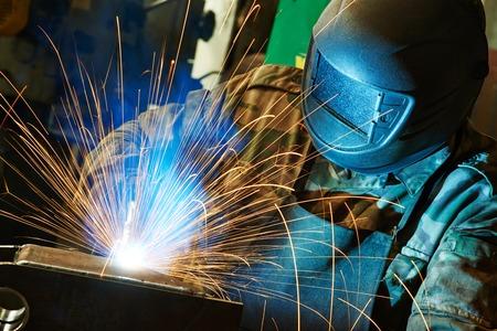 soldadura: soldador de trabajo con el electrodo en la soldadura por arco semi-automática en la fabricación de la planta de producción