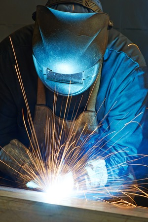 soldering: welder working with electrode at semi-automatic arc welding in manufacture production plant