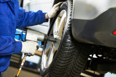 car mechanic screwing or unscrewing car wheel of lifted automobile by pneumatic wrench at repair service station photo