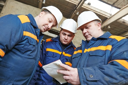 housebuilding: three industrial engineer chief discussing enterprise development in house-building plant