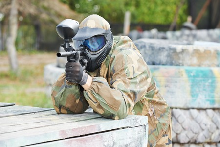 27626375: paintball sport player man in protective camouflage uniform and mask with marker gun outdoors