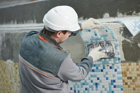tiler: industrial tiler builder worker installing floor tile at repair renovation work