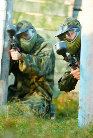 Two paintball sport players in prootective uniform and mask aiming and shoting with gun outdoors photo