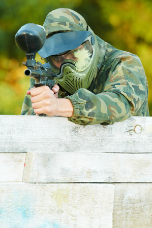 gunfire: Two paintball sport players in prootective uniform and mask aiming and shoting with gun outdoors