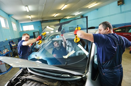 replacement: Automobile glaziers workers replacing windscreen or windshield of a car in auto service station garage