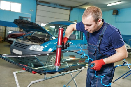 glazier: Automobile glazier adding glue on windscreen or windshield of a car in auto service station garage before installation Stock Photo