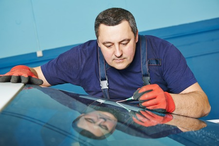 window repair: Automobile glazier repair windscreen or windshield of a car in auto service station garage Stock Photo