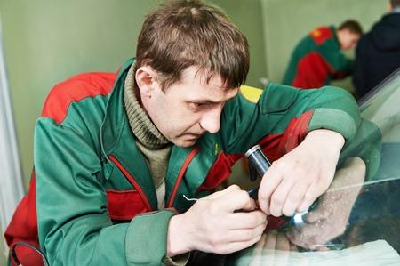 glasscutter: Automobile glazier repairman examining windscreen or windshield of a car in auto service station garage