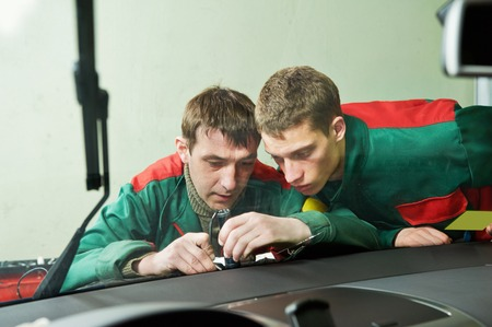 Automobile glazier repairman teaching or discussing with partner windscreen repair of a car in auto service station garage photo