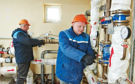 boiler house: repairman engineer of fire engineering system or heating system open the valve equipment in a boiler house