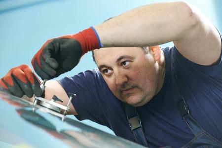 glasscutter: Automobile glazier repair windscreen or windshield of a car in auto service station garage Stock Photo