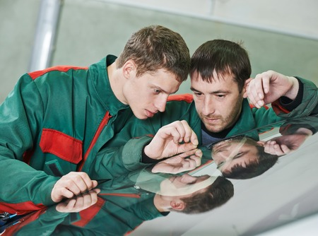 Automobile glazier repairman teaching or discussing with partner windscreen repair of a car in auto service station garage Stock Photo - 27908409