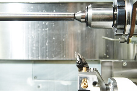 affixment: industrial metal work machining process by cutting tool on automated lathe Stock Photo
