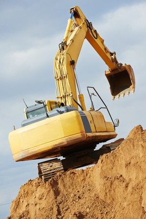 roadwork: excavator machine at excavation earthmoving work in sand quarry Stock Photo