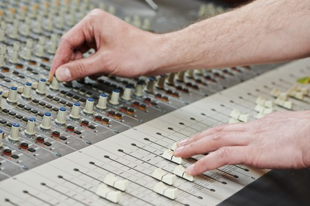 close-up hands of sound engineer work with faders on mixer photo