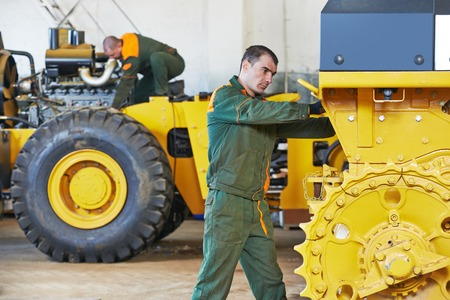 industrial worker during heavy industry machinery assembling on production line manufacturing workshop at factory photo