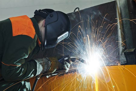 electrode: welder working with electrode at semi-automatic arc welding in manufacture production plant