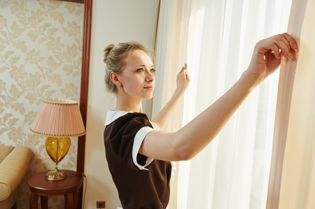 Hotel service. female housekeeping chambermaid worker with opening curtains of window in room photo