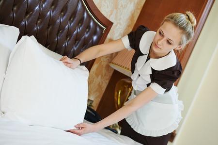 ホテル サービス。女性ハウスキーピング ワーカー メイド イン部屋で布団のベッドを作り 写真素材