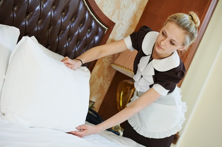 Hotel service. female housekeeping worker maid making bed with bedclothes at inn room Фото со стока