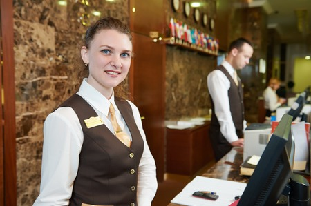 Happy female receptionist worker standing at hotel counter Banco de Imagens