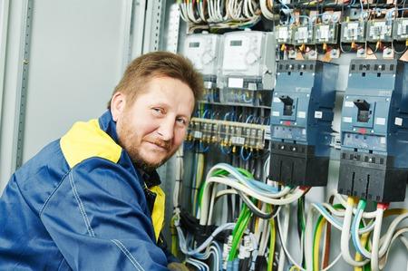 circuito electrico: Feliz joven ingeniero constructor electricista adulta haciendo medida eléctricos con equipos en fuseboard