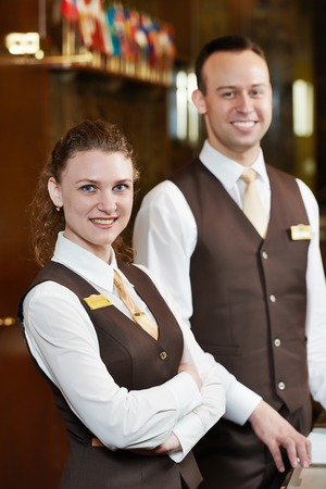 Happy receptionist workers standing at hotel counter photo