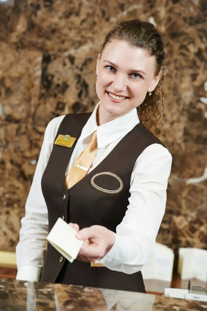 smiling female receptionist passing key card to guest photo