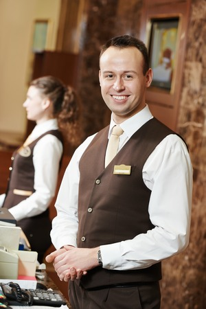 hotel staff: Happy receptionist worker standing at hotel counter Stock Photo