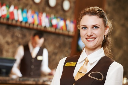 hotel staff: Happy receptionist female worker portrait standing at hotel counter in lobby