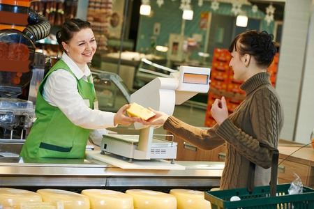 Sales assistant in supermarket demonstrating food cheese to female customer during shopping at store photo
