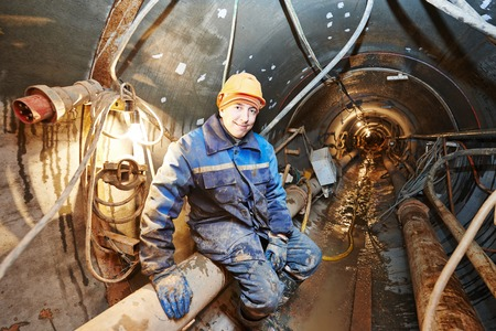 mounter: Tunneller sinker worker connecting equipment in tunnel of sewer collector at undergroung working