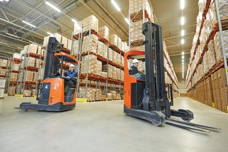 storage warehouse: two young workers men in uniform at warehouse with forklift facilities Stock Photo