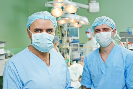 cardiosurgery: happy surgeons in uniform perform heart transplantation operation on a patient at cardiac surgery clinic Stock Photo