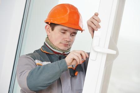 Male worker handyman carpenter at lock installation into wood door