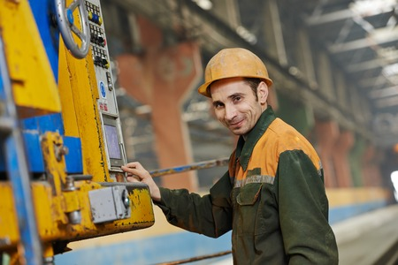 metalworker: industrial worker operating concrete machine at factory workshop Stock Photo