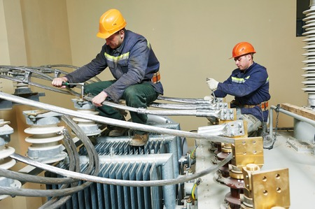 Electrician lineman repairman worker at huge power industrial transformer installation work photo