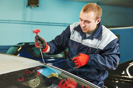 car glass: Automobile glazier worker replacing windscreen or windshield of a car in auto service station garage Stock Photo