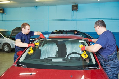 replacements: Automobile glaziers workers replacing windscreen or windshield of a car in auto service station garage