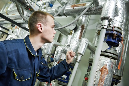boiler house: repairman engineer or inspector of fire engineering system or heating system with valve equipment in a boiler house