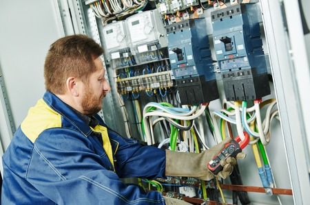 installation: adult electrician builder engineer in front of equipment in fuseboard Stock Photo