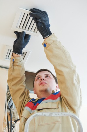 industrial builder installing ventilation or air conditioning filter holder in ceiling photo